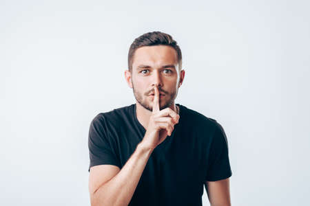 Foto de Young man holding index finger on lips asking for silence.  Secret concept - Imagen libre de derechos