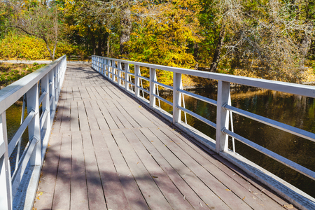 Photo pour Wooden foot bridge with metal railings over the river a bright autumn day - image libre de droit