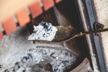 Foto de Cleaning the fireplace. Ash and charred piece of wood lying on the blade with a long handle closeup  - Imagen libre de derechos