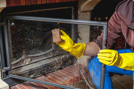 Foto de Cleaning the fireplace. Hands in yellow rubber gloves wash the glass smoked fireplace door with a sponge - Imagen libre de derechos