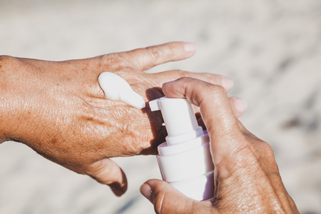 Photo pour Elderly woman smears her hands with sunscreen from a container on the summer sea beach - image libre de droit