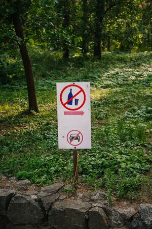 Foto de Drinking alcohol is prohibited. A white shield with pictograms indicates a resting place in the forest. Pedestrian zone - Imagen libre de derechos