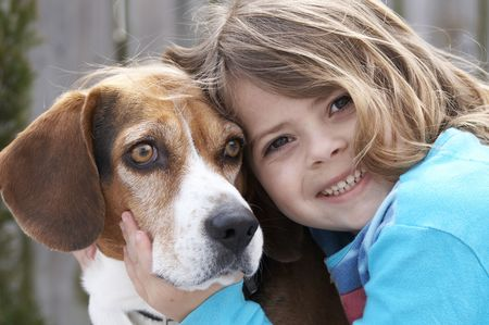 a cute picture of a young beagle and a little girl
