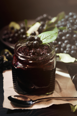 Photo pour Jam from black chokeberries ( Aronia melanocarpa ) and its berries on dark table. Homemade preserves. Vertical. - image libre de droit