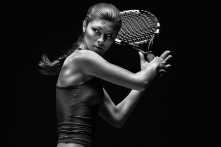 Female tennis player.  Female tennis player holding racket behind head, isolated on black background.