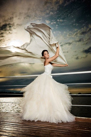 Foto de Fiancé in the wind. Pretty lady in a wedding dress on deck. - Imagen libre de derechos