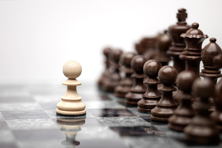 Photo for One pawn staying against full set of chess pieces. - Royalty Free Image