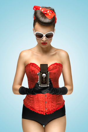 Photo pour A photo of the pin-up girl in corset holding vintage camera  - image libre de droit