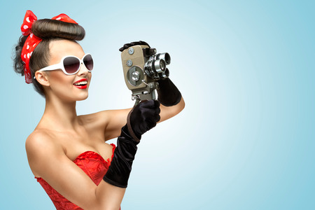 Photo pour A photo of the pin-up girl in corset and gloves holding vintage 8mm camera  - image libre de droit
