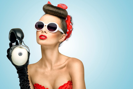 Photo pour The retro photo of a cute pin-up girl in sunglasses with vintage music headphones  - image libre de droit