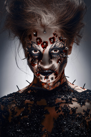 Photo for A creepy halloween makeup of a witch with a bloody peircing and cracked face paint. - Royalty Free Image