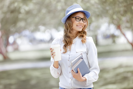 Photo pour Happy young woman with a coffee-to-go, walking in a summer park and holding books for reading. - image libre de droit
