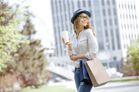 Photo for Happy young trendy woman drinking take away coffee and walking with shopping bags after shopping in an urban city. - Royalty Free Image