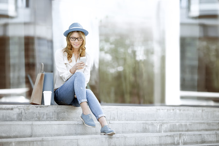 Foto de Happy young woman with a disposable coffee cup and shopping bags sitting on the stairs and using her smartphone for communication via wi-fi internet in a summer park. - Imagen libre de derechos