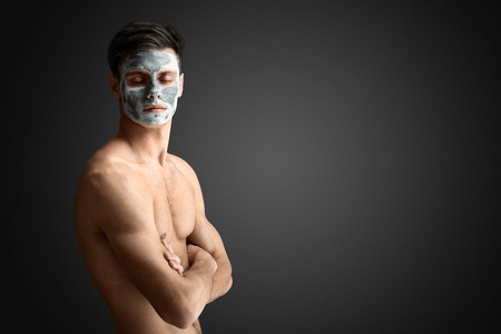 Photo for Portrait of a beautiful young man with a facial mud clay mask, face and body skin care treatment. - Royalty Free Image