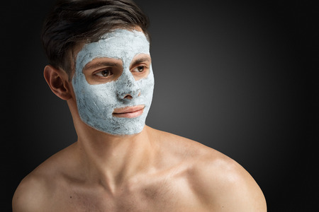 Foto de Portrait of a beautiful relaxed young man with a facial mud clay mask, face and body skin care treatment. - Imagen libre de derechos