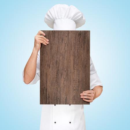 Foto de Restaurant chef hiding behind a wooden chopping board for a business lunch menu with prices. - Imagen libre de derechos