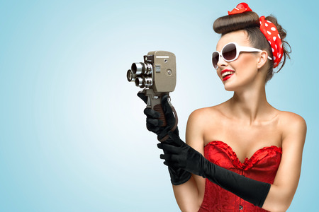 Photo for A photo of the pin-up girl in corset and gloves holding vintage 8mm camera. - Royalty Free Image