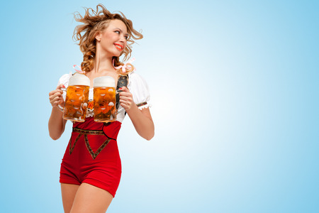 Foto de Young smiling sexy Swiss woman wearing red jumper shorts with suspenders in a form of a traditional dirndl, holding two beer mugs and looking aside on blue background. - Imagen libre de derechos