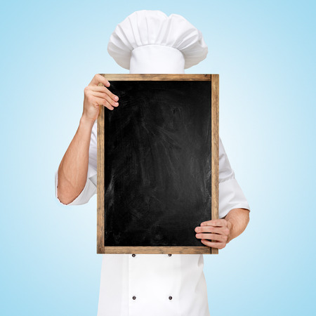 Foto de Restaurant chef hiding behind a blank chalkboard for a business lunch menu with prices. - Imagen libre de derechos