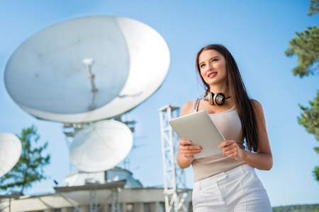 Foto de Beautiful young woman with vintage music headphones around her neck, surfing internet on a tablet pc and standing against background of satellite dishes that receives wireless signals from satellites. - Imagen libre de derechos