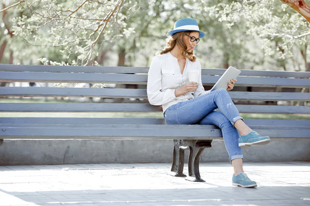 Photo pour Happy young student with a tablet and a disposable coffee cup sitting on the bench and reading in a summer park. - image libre de droit