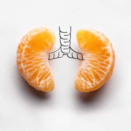 Foto de A health concept of unhealthy human lungs of a smoker with lung cancer in dark shadows, made of mandarin segments. - Imagen libre de derechos