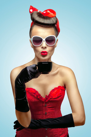 Photo pour The vintage photo of glamour pin-up girl wearing vintage gloves and cooling a hot cup of coffee. - image libre de droit