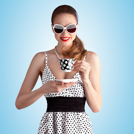 Photo pour Creative vintage portrait of a beautiful pin-up girl holding a teacup and drinking tea on blue background. - image libre de droit