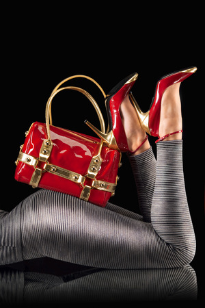 Photo pour Red handbag and high-heeled shoes on female butts. - image libre de droit