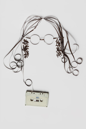 Photo pour A beautiful image made of tape cassette with the tape forming a face of hair glasses on bright background. - image libre de droit