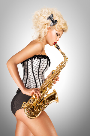 Photo for Beautiful pinup model playing saxophone on grey background. - Royalty Free Image