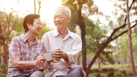Photo pour Healthy Asian senior couple drinking coffee in morning park together - image libre de droit