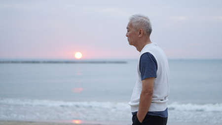 Photo for Asian senior man standing at sunrise ocean thinking about life - Royalty Free Image
