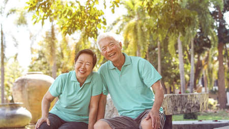 Foto de Asian elderly couple laugh together in green natural park background - Imagen libre de derechos