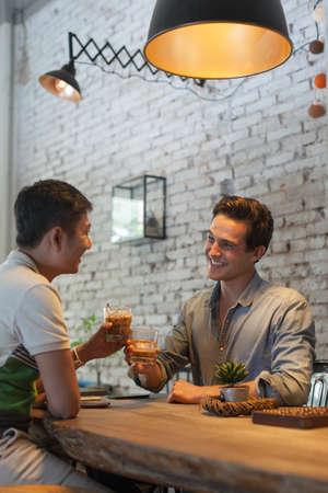 Foto de Two Men Cheers Toast Drink Ice Coffee, Asian Mix Race Friends - Imagen libre de derechos