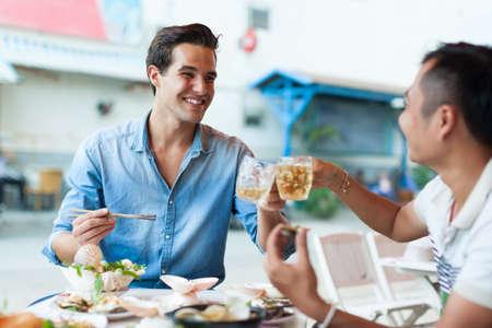 Photo pour Tourist Men Cheers Toast Drink, Asian Mix Race Friends - image libre de droit