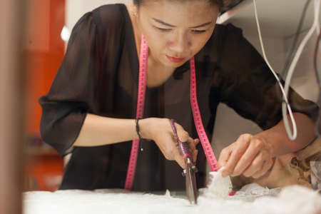 Photo pour Asian woman tailor fashion clothes dress designer working with scissors fabric - image libre de droit