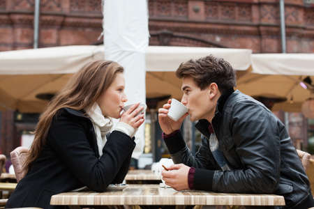 Photo pour Side view of young couple drinking coffee together at outdoor restaurant - image libre de droit