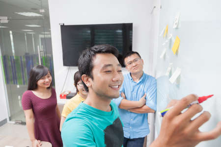 Foto de Asian business people team drawing on white wall whiteboard with sticky notes creative real office - Imagen libre de derechos