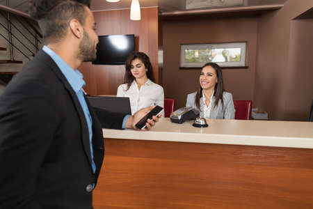 Foto de Business Man Arrive To Hotel Check In With Cell Phone Woman Receptionist Registration At Reception Counter - Imagen libre de derechos