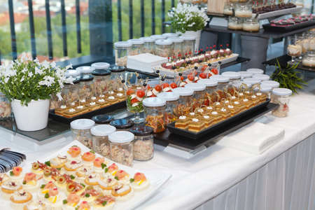Foto de Beautifully decorated catering banquet table with different food snacks and appetizers - Imagen libre de derechos
