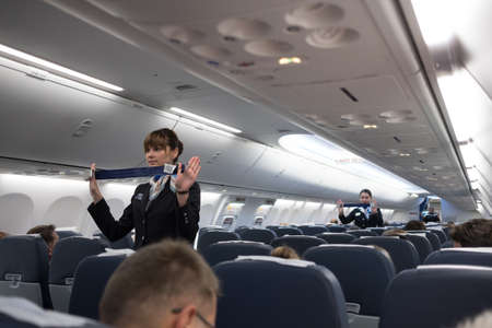 Foto de St. Petersburg, Russian Federation - October 16, 2017:  Stewardesses  in the cabin of the 737-800 passenger airplane instruct passengers on safety measures and  in the event of an emergency - Imagen libre de derechos