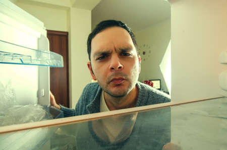 Foto de hungry man with funny face opens the fridge - Imagen libre de derechos