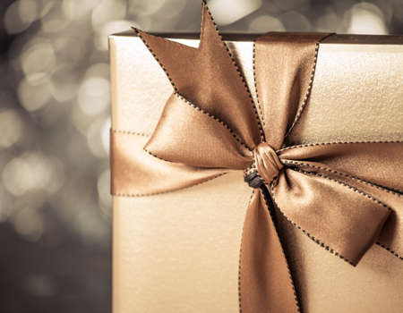 gift box with golden ribbon, glittery gold background