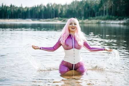 Foto de Sexy woman in transparent purple latex outfit posing in the water - Imagen libre de derechos