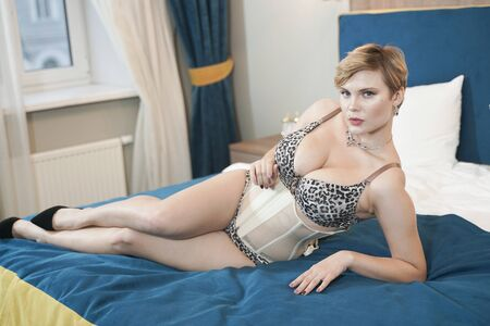 Photo for stylish pin up short hair blonde woman with plus size curvy body posing in fashion leopard underwear in the bedroom alone - Royalty Free Image