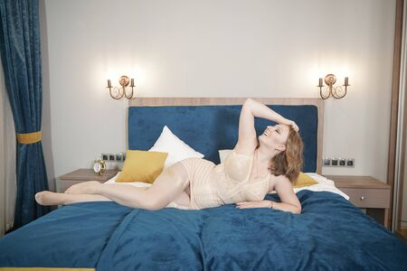 Photo pour Voluptuous beautiful young curvy woman wearing retro beige lingerie with vintage stockings with seam. Adult sexy plus size girl in lingerie on the bed. - image libre de droit