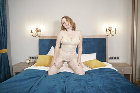 Photo for Voluptuous beautiful young curvy woman wearing retro beige lingerie with vintage stockings with seam. Adult sexy plus size girl in lingerie on the bed. - Royalty Free Image