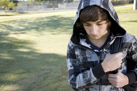 Teenage student (15 years) carrying bookbag on shoulder, looking down with serious expression